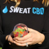 Woman holding sweat cbd gummy bears